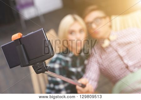 Cheerful loving couple is making selfie on mobile phone. They are sitting and sending kiss to the camera. Man is holding a stick. Focus on technology