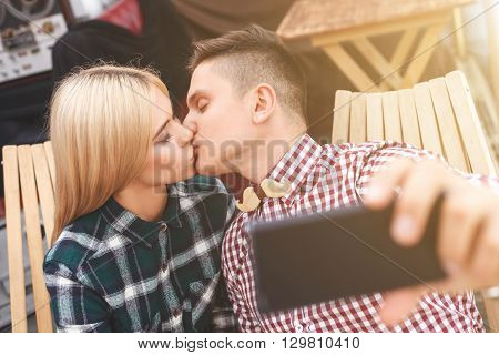 Cute loving couple is making selfie wile kissing. Man is sitting and holding a mobile phone. They eyes are closed with love