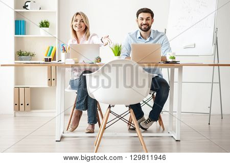 Have a sit. Skillful young colleagues are working in office with joy. Woman is pointing her arm on chair with invitation. Man is sitting and smiling