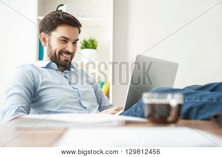 Handsome young man is typing on laptop and smiling. He is sitting at desk with relaxation