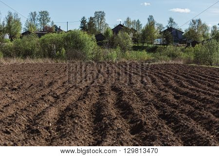 Colours of spring - plouged field ready to sow. Agriculture concept.