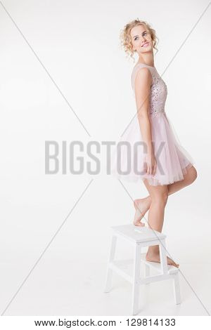 Lovely curly women lookin on copyspace in pink shot dress. Isolated on white background