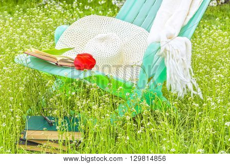 Relax in the blooming spring garden with a book on a sunny day on a green lawn close-up