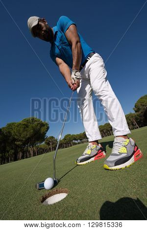 golf player hitting shot with driver on course at beautiful sunny day with wide angle lens