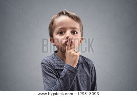 Boy with finger on lips making a silent gesture