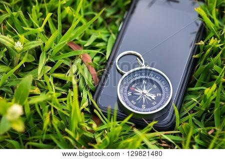 Compass with smart phone on the field. conceptual of global travel , tourism and exploration, with copy-space.