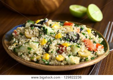Quinoa salad with sweet corn olive tomato cucumber and chives on plate photographed on dark wood with natural light (Selective Focus Focus in the middle of the salad)
