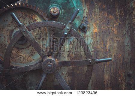 Vintage tinted snapshot of  ancient gears mechanism. Steampunk background. Rusty metal wheel.