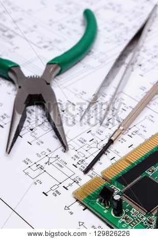 Printed circuit board with electrical components and precision tools lying on construction drawing of electronics drawings and precision tools for engineer jobs technology