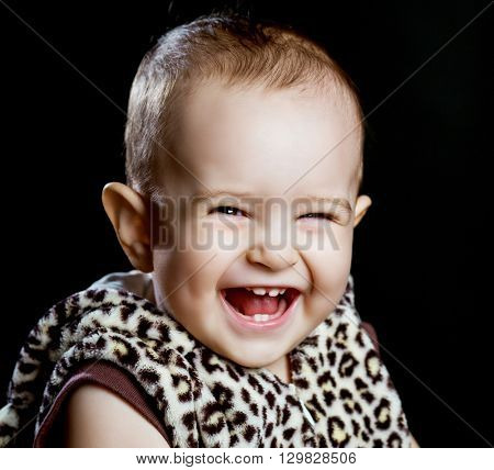 happy laughing one year old baby, isolated against black background