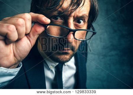 Angry tax inspector looking serious and determined adult businessperson with glasses