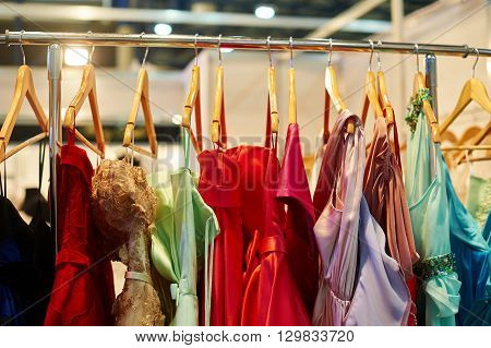 Evening dresses hang on a shelf in a store.
