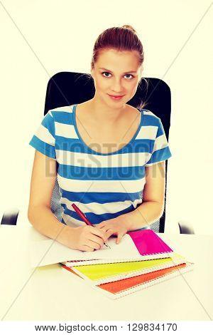 Teenage woman doing homework behind the desk poster