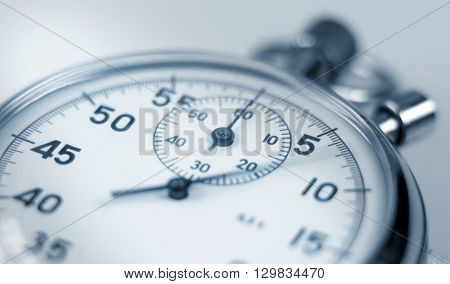 Analog stopwatch close-up with blurred second hand.