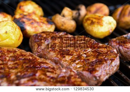 delicious grilled rump steak with mushrooms and potatoes on barbecue