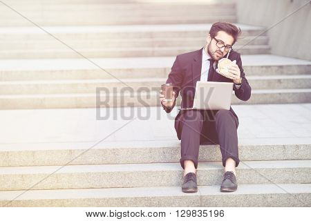 Toned picture of businessman speaking on mobile or smart phone while sitting on stair in city centre and working on laptop computer. Freelance man drinking cup of coffee or tea.