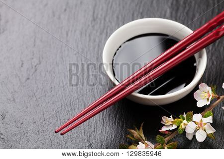 Japanese sushi chopsticks, soy sauce bowl and sakura blossom on black stone background. Top view with copy space