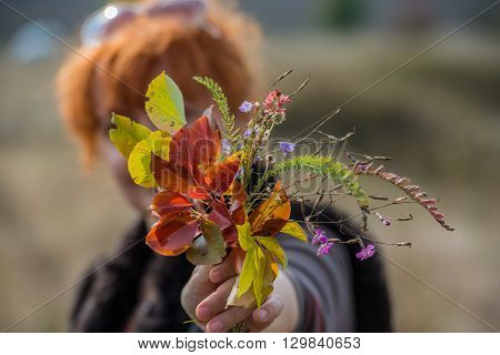 woman with a bouquet outdoors autumn colors