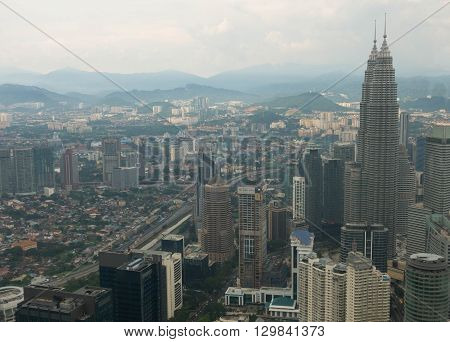 KUALA LUMPUR MALAYSIA - MAY 10 2016 : Kuala Lumpur skyline with the Petronas Towers and other skyscrapers. Aerial view from the Menara Kuala Lumpur Tower.