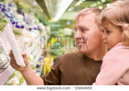 Smiling young man with little girl buy parsley in supermarket