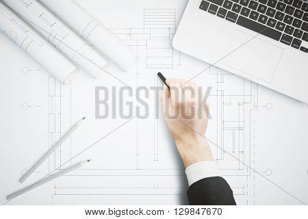 Hand drawing architectural project on large whatman with pencils and laptop computer on top. Architectural concept. Business man hand drawing construction sketch