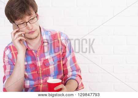 Young man with coffee cup in hand talking on mobile phone with white brick wall in the background