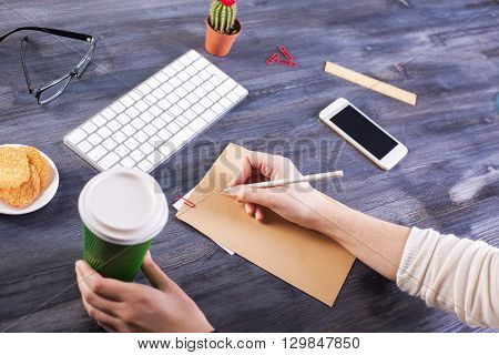 Top view of girl's hands holding coffee cup and writing on brown paper placed on wooden desktop with blank smart phone keyboard cactus and other items. Mock up
