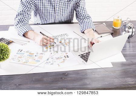 Business idea concept with man using laptop and drawing business sketches on wooden desktop with various items. White brick wall background