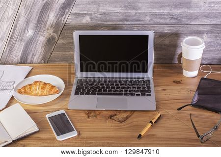 Wooden desktop with blank laptop screen croissant smartphone and other items. Mock up