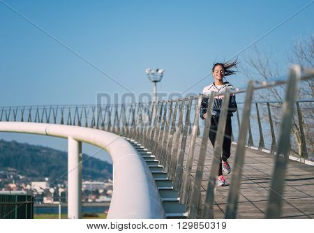 Beautiful Hispanic Woman Running On A Bridge