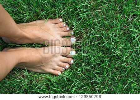 Barefoot girl on the soft summer grass.