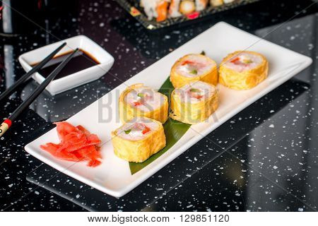 Sushi roll with scallop and Tomago on white plate on blabk table