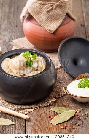 Meat Dumplings - russian pelmeni with sour cream on rustic background