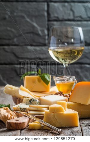 Various types of cheese  on cutting board with white wine on wooden background
