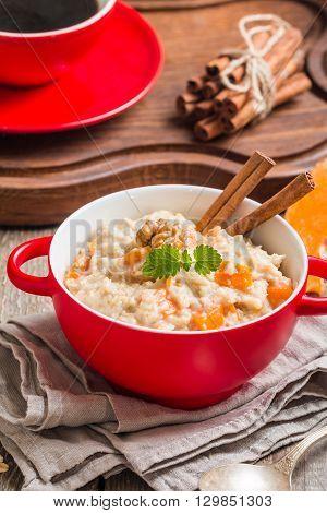 Breakfast oatmeal porridge with pumpkin in red bowl on wooden background