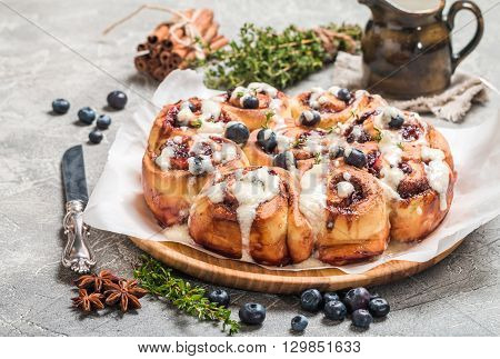 Cinnamon buns with lemon, blueberry and thyme on gray background