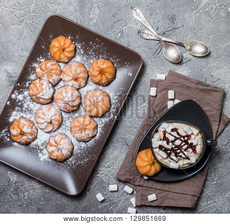 Plate with biscuit cookies and cup of hot coffee on old gray background. Top view