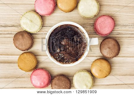 Cup of black coffee with tasty french colorful macarons in the circle shape. Sweet delight. View from above. Close up. Sweet macarons.