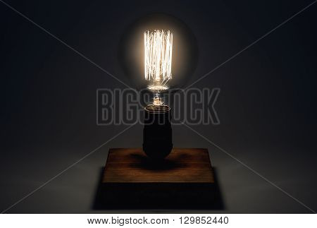 Edison Lamp with filament on a wooden stand. Lighthouse concept.