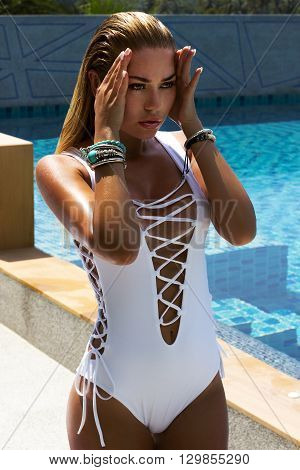 Woman in white swimsuit posing near swimming pool. Beautiful stylish tan girl. Summer on island. Phuket, Thailand.