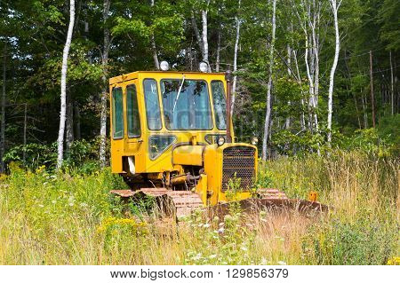 NOVA SCOTIA CANADA - 27TH AUGUST 2014: A small bright yellow tractor parked in a field.