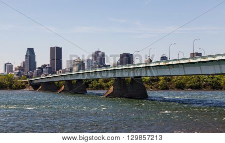A view of downtown Montreal during the day showing the Pont de la Concorde bridge buildings and offices.
