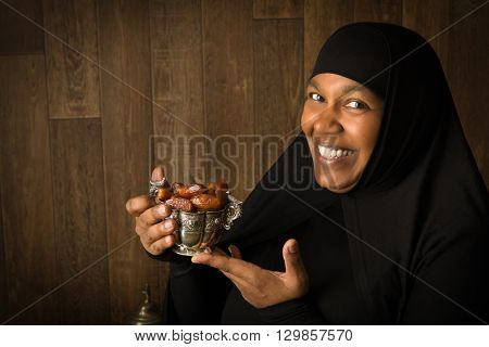 African muslim woman in black veil presenting traditional sweet dates