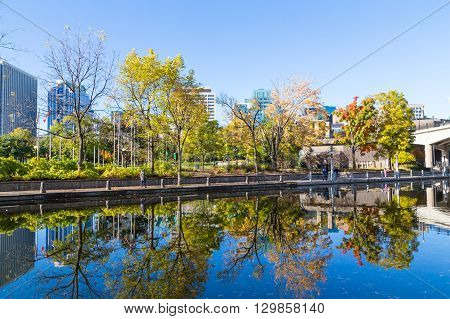OTTAWA CANADA - 12TH OCTOBER 2014: Trees and Reflections in the Rideau Canals during the fall. People can be seen.
