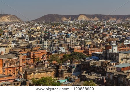 High view over the city of Jaipur in India showing lots of buildings and hills in the distant.