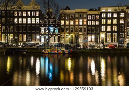 AMSTERDAM NETHERLANDS - 17TH FEBRUARY 2016: Amsterdam buildings and a colorful boat in the canal at night. Reflections can be seen.