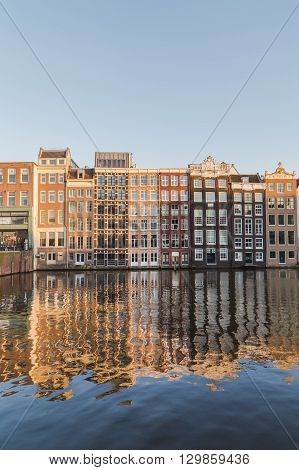 AMSTERDAM NETHERLANDS - 16TH FEBRUARY 2016: Old Buildings along the Damrak in Amsterdam during the day.