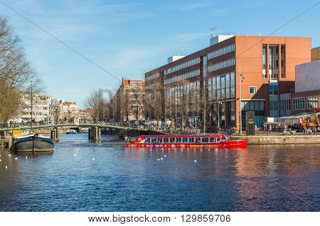 AMSTERDAM NETHERLANDS - 16TH FEBRUARY 2016: A City Sightseeing Boat in the Amsterdam Canals. Passengers can be seen on the boat. Buildings bikes and people can be seen in the background.
