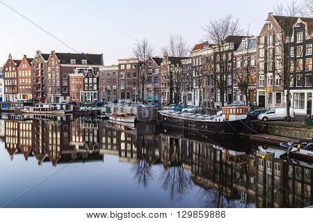 A view along the Waalseilandgracht Canal in Amsterdam in the morning. Building boats and reflections can be seen. There is space for text.