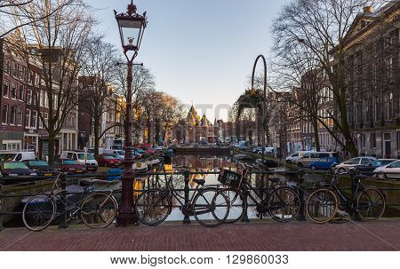 """AMSTERDAM NETHERLANDS - 16TH FEBRUARY 2016: A view towards The Waag (""""weigh house"""") in Amsterdam from the Kloveniersburgwal canal. People cars bikes and other buildings can be seen."""